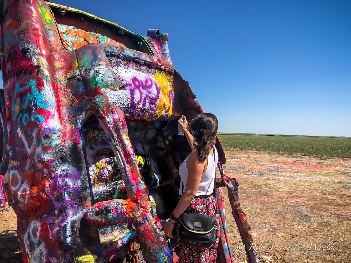 Picking up a can and spraying one of the cars at Cadillac Ranch is one of the best things to do in Amarillo, Texas