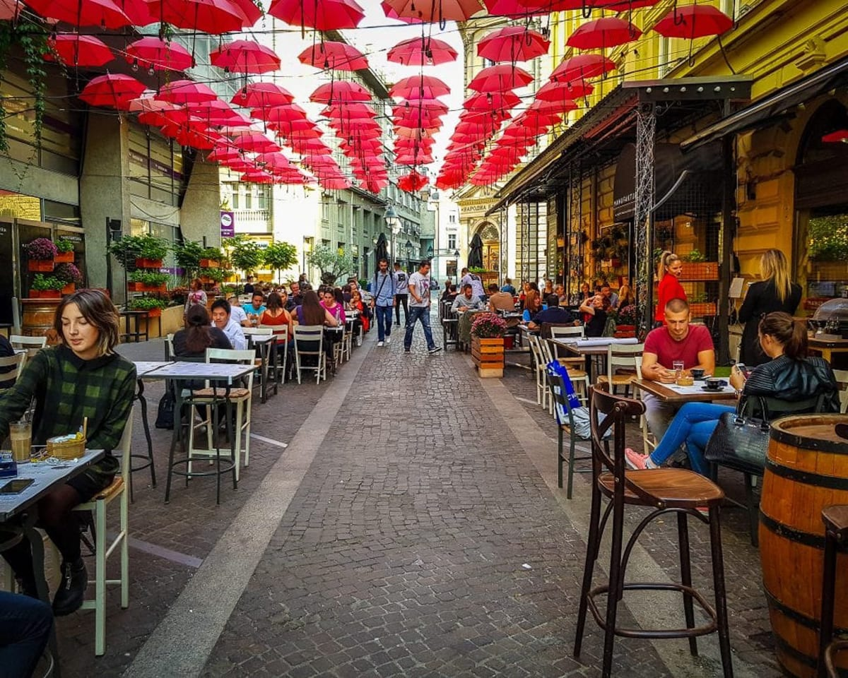 Have lunch in Belgrade at one of the restaurants under the bright red umbrellas at Manufaktura